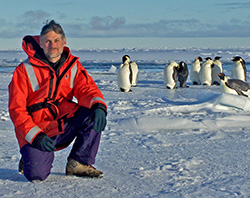 Pat Neal at the South Pole with penguins.
